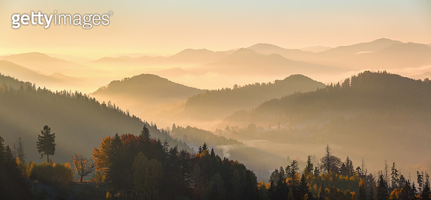 Panorama with interesting sunrise enlightens surroundings. Landscape with beautiful mountains, fields and forests covered with morning fog. Fantastic autumn rural scenery. Picturesque resort.