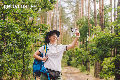 Smiling female tourist holds smart phone, takes selfie against beautiful landscape wood. Hiking woman with backpack taking selfie photo with smartphone. Travel and healthy lifestyle outdoors