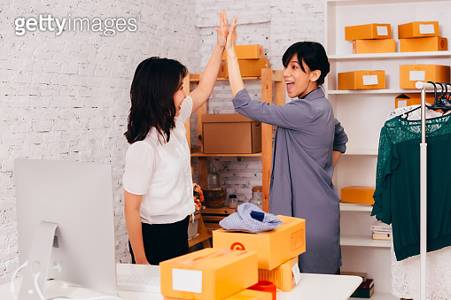 Asian businesswomen giving high five in office