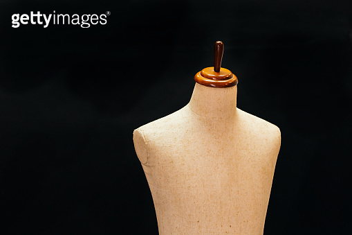 Old and vintage mannequin made of cloth standing in black background lid in 3d - can be used for tailoring and garment concept.
