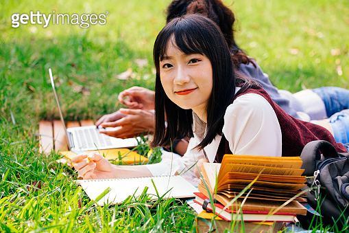 Young adolescent university female student looking at camera and having a group of friends hangout in nature park