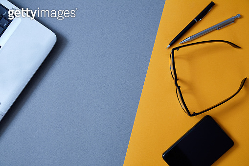 Blogging, blog and blogger or social media concept: a laptop, glasses and an external hard drive on a grey and yellow background. Flat lay