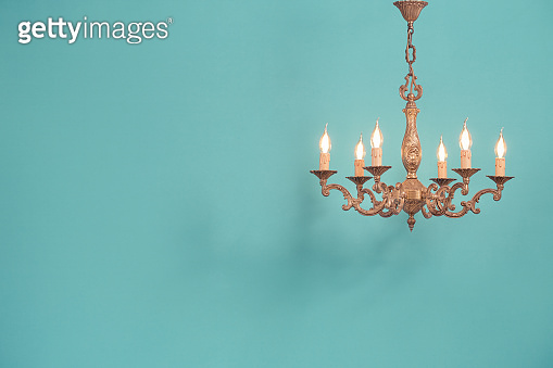 Retro antique old bronze chandelier with bulb lamps shaped candles hanging front mint blue wall background. Nostalgia lighting concept. Vintage style filtered photo