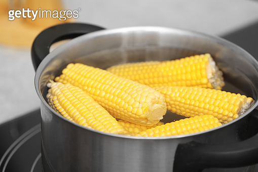 Stewpot with water and corn cobs on stove, closeup