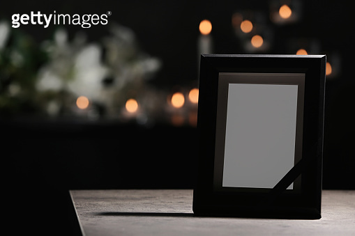 Funeral photo frame with black ribbon on table in dark room