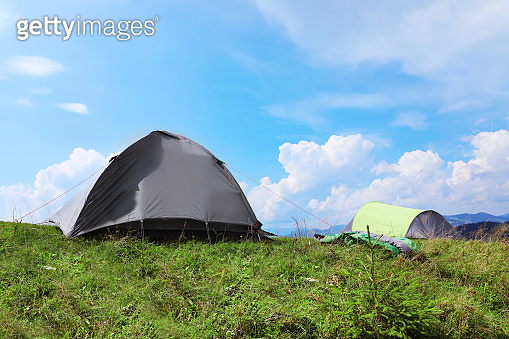 Small camping tents in mountains on sunny day