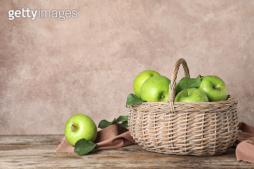 Composition with juicy green apples in wicker basket on table. Space for text