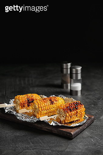 Delicious grilled corn cobs on table against black background. Space for text