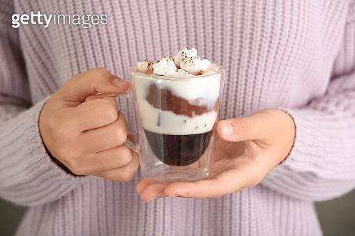 Woman holding chocolate dessert with marshmallows, closeup