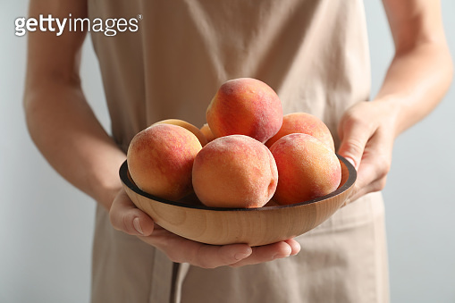 Woman holding plate with fresh sweet peaches, closeup