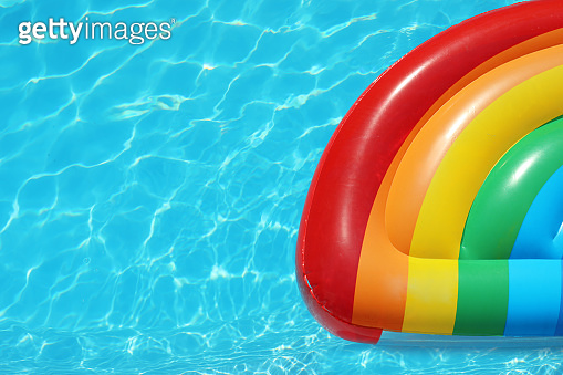 Inflatable mattress floating in swimming pool on sunny day, top view. Space for text