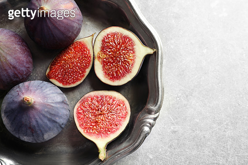 Dish with fresh ripe figs on gray background, top view. Space for text