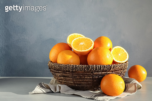 Fresh juicy oranges in wicker basket on table. Space for text