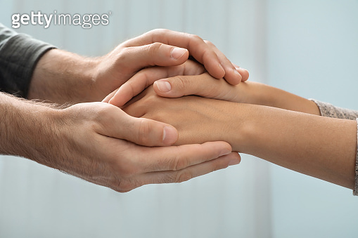 Man holding woman's hands against blurred background, closeup. Concept of support and help