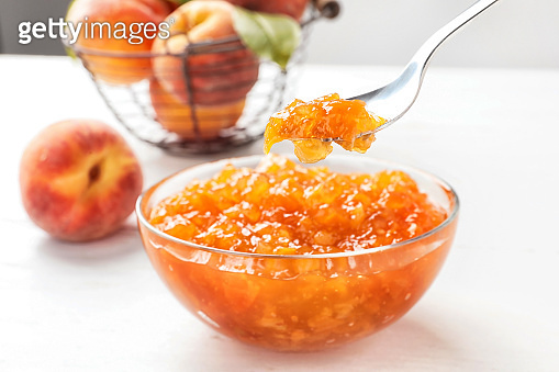 Bowl and spoon with peach jam on table