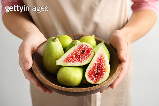 Woman holding bowl with fresh ripe figs on light background