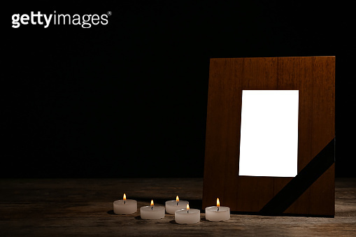 Empty frame with black ribbon and candles on table. Funeral symbol