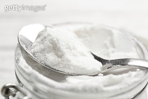 Jar and spoon with baking soda, closeup