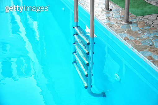 Modern swimming pool with stairs at resort