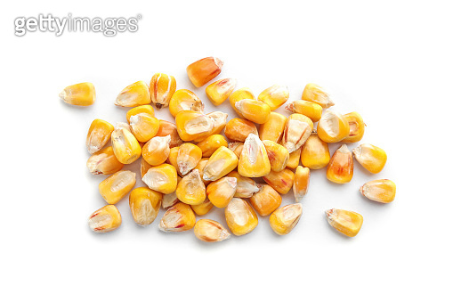 Dried corn kernels on white background, top view