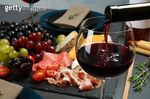 Pouring red wine into glass on served table, closeup. Space for text