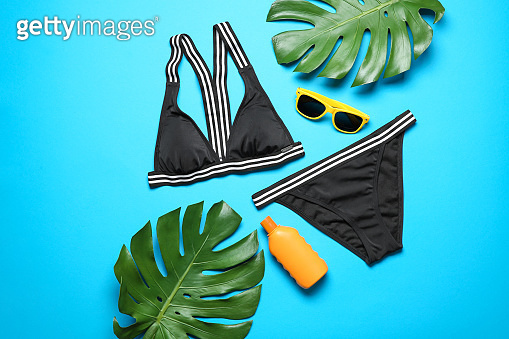 Flat lay composition with bikini and beach objects on color background