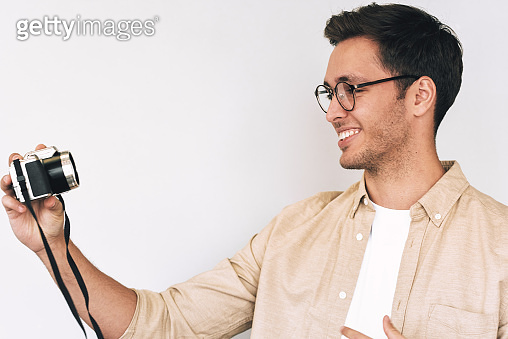 Side view portrait of cheerful young man freelancer taking selfie over white studio background and looking to his digital camera. Young male smiling and wearing eyewear making self portrait, blogging