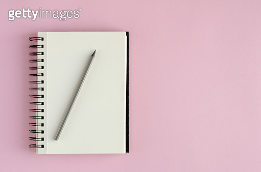 Note pad with pencil composition on pink background.