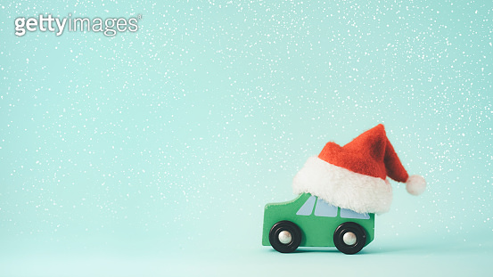 The wooden toy car and Santa Claus hat on snow and mint color background.
