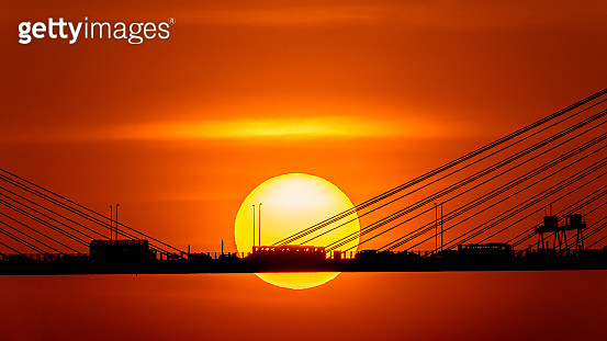 Sunset over the cable-stayed bridge with silhouette of car crossing the sea bay