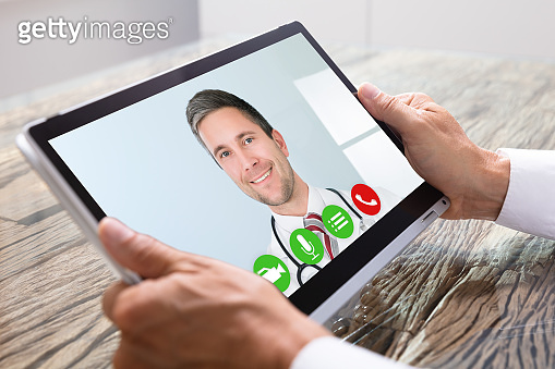 Person Videochatting With Doctor On Digital Tablet