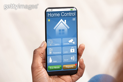 Person Using Home Control System On Mobile Phone