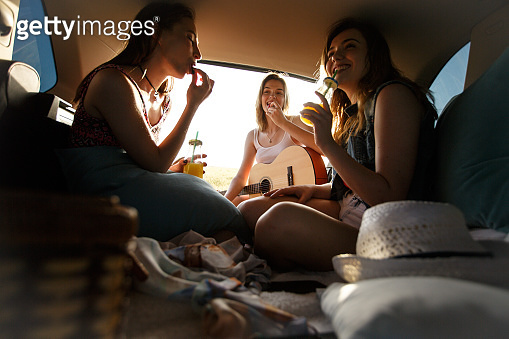 Happy group of girlfriends enjoying while food and beverages on their road trip
