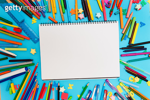 Blank sketchbook page surrounded by art materials