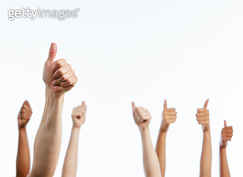 Seven raised hands give enthusiastic hands-up signals on white