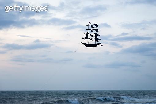 Black sailing ship kite at a beach near Puna Tanah Lot temple, Bali, Indonesia