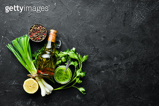 Ingredients for chimichurri sauce: fresh parsley, onion, garlic, olive oil, lemon. On a black background. Top view. free space for your text.