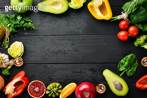 Fruits and vegetables containing fiber: Avocados, kiwi, apple, tomatoes, spinach, paprika, orange, lemon. Top view. Free space for your text. On a black background.