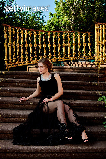 Young attractive woman in the sexy transparent black dress. Young woman portrait.