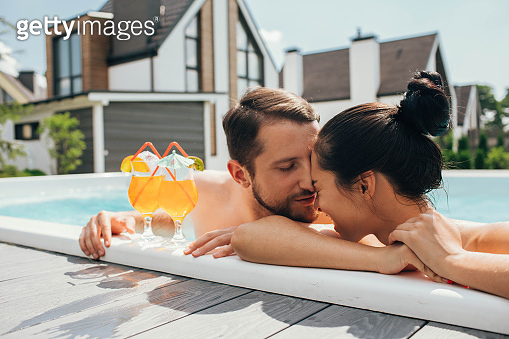 happy heterosexual couple is well rested with cocktails while in the pool. Summer rest