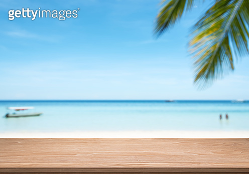 Empty wooden table with blurred tropical beach background