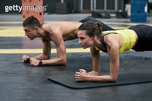 Fitness couple doing plank exercise workout in outdoor gym