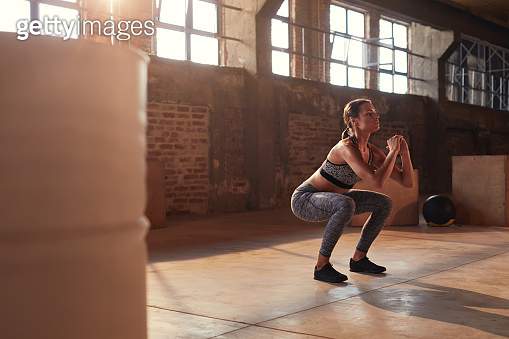 Fitness workout. Sport woman doing squat leg exercise at gym