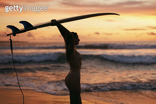 Summer. Surfer girl silhouette with surf board on sunset beach