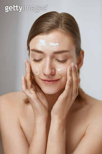 Face skin care. Woman applying facial cleanser on face closeup