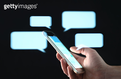 Text messages in cellphone screen with abstract hologram speech bubbles. Instant messaging app. Texting, group chat, sexting or sms concept.
