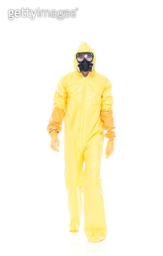 Full length / one person of 20-29 years old adult handsome people / slim caucasian male / young men walking in front of white background wearing protective workwear / gas mask / mask - disguise / radiation protection suit / protective suit