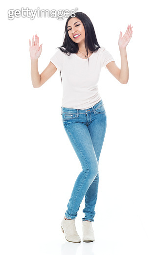 Full length / one person / front view of 20-29 years old adult beautiful / long hair latin american and hispanic ethnicity female / young women standing in front of white background wearing jeans / t-shirt / shirt / cool attitude and greeting