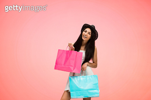 Beautiful female on pink background and is holding shopping bags