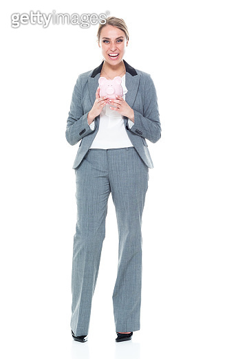 One person / full length / front view of 20-29 years old adult beautiful caucasian female / young women businesswoman / business person standing wearing a suit who is smiling / happy / cheerful / successful and holding piggy bank / currency